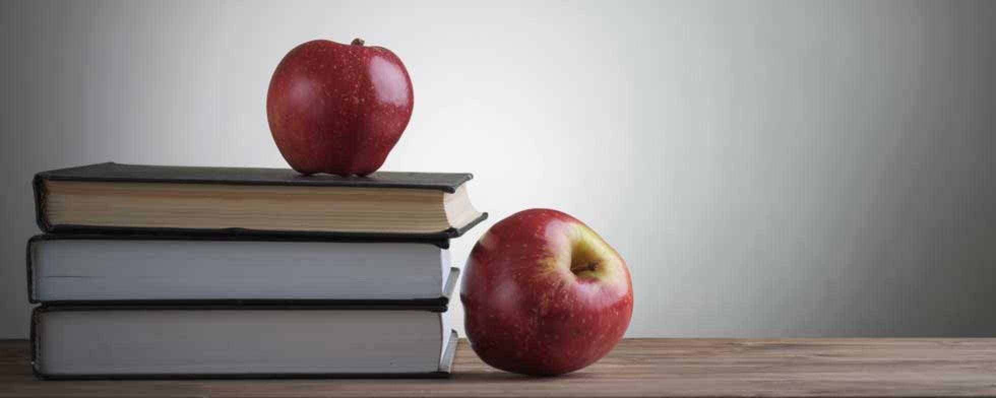 Books and two apples on a desk.